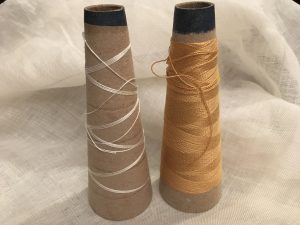 White (almost out) and gold silk yarn on cones.